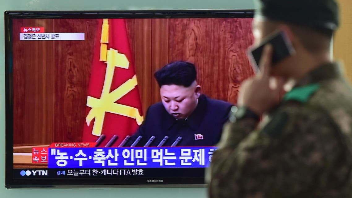 A South Korean soldier talks over his phone in front of a television screen showing North Korean leader Kim Jong-Un's New Year speech, at a railroad station in Seoul on January 1, 2015. AFP