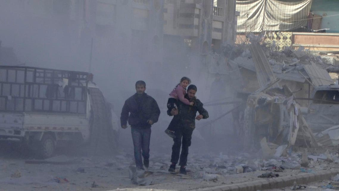 A man carries a girl past damage at a site hit by what activists said was an air strike by forces loyal to Syria's President Bashar al-Assad in the northwestern Homs district of Al Waer Dec. 30, 2014.  (Reuters)