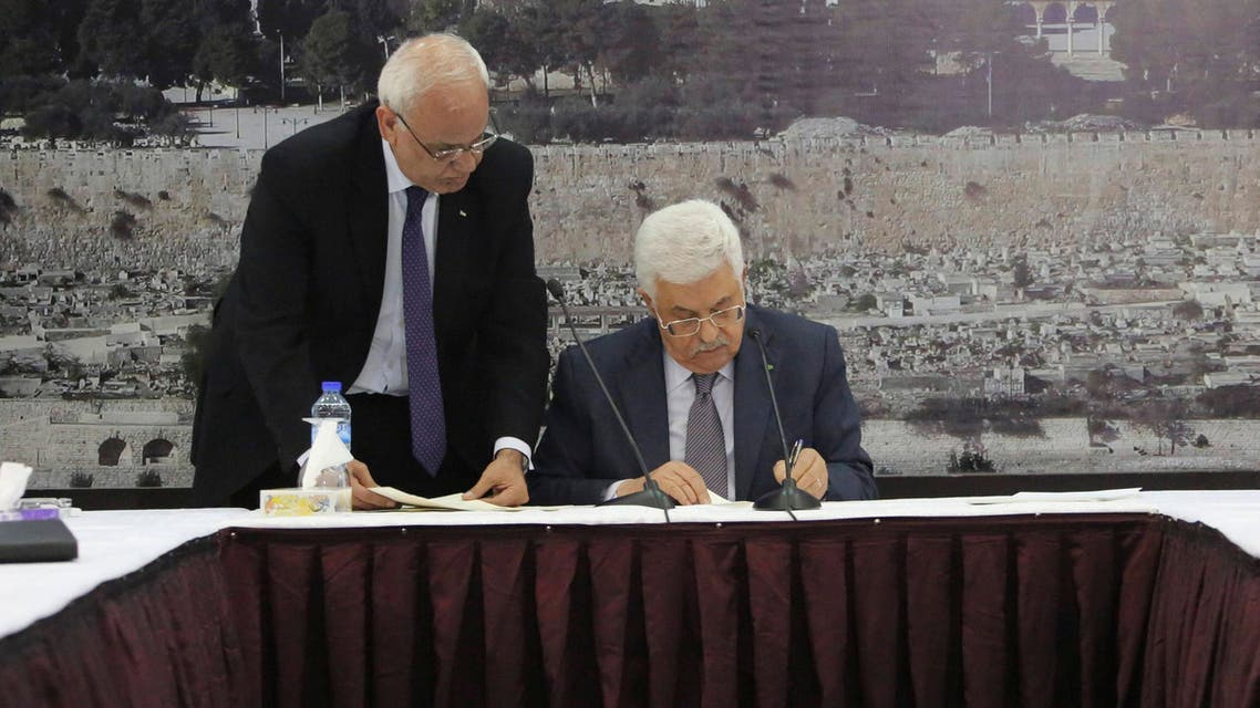 Palestinian President Mahmoud Abbas (R) signs international agreements in the West Bank city of Ramallah, in this Dec. 31, 2014 handout picture. (Reuters)