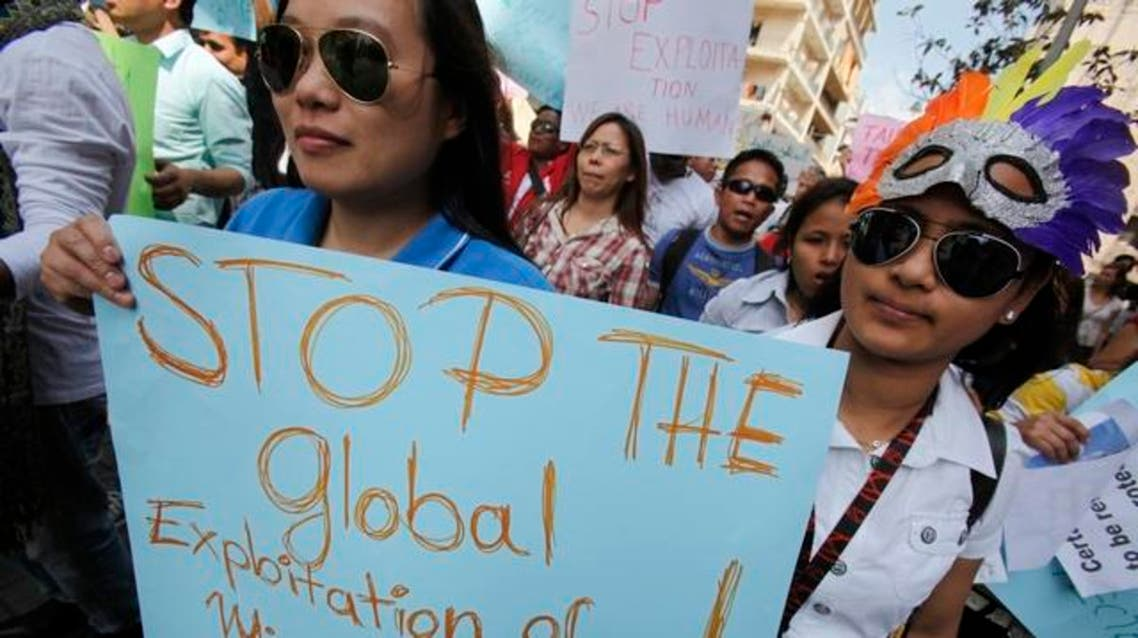 Migrant workers hold placards during a demonstration to support the rights of migrant domestic workers on International Workers' Day or May Day, in Beirut on May 1, 2011. (c) 2011 Reuters