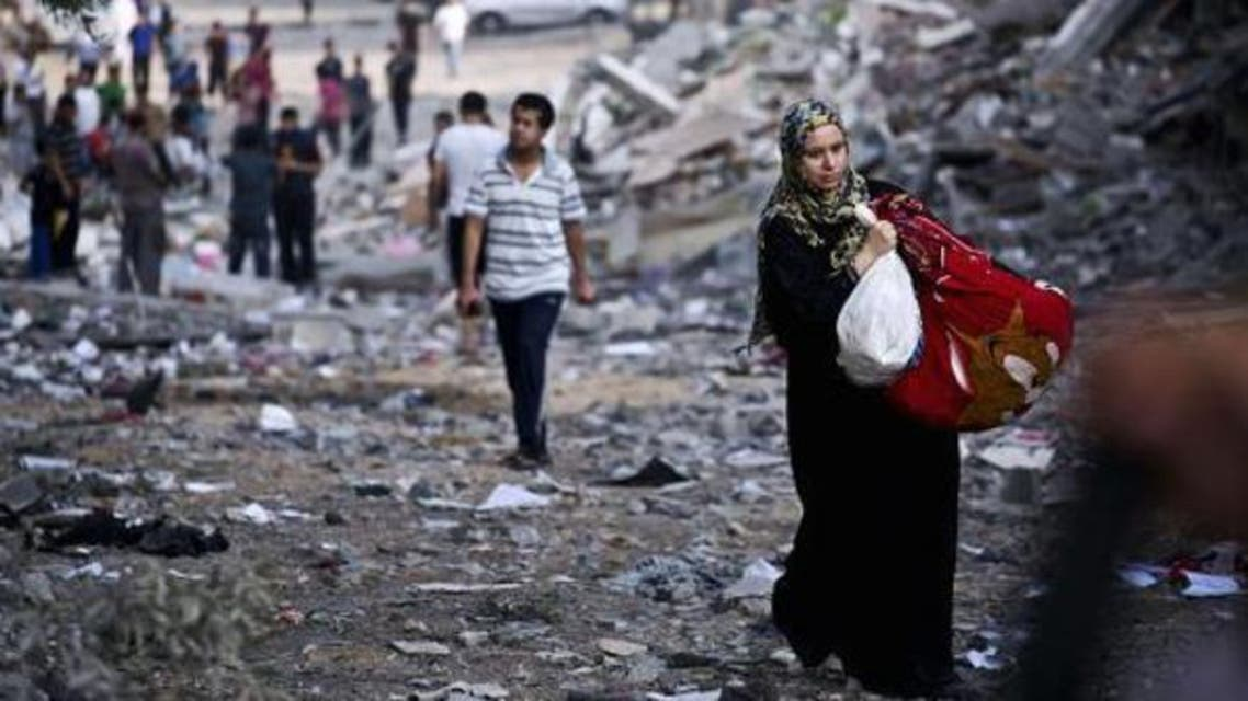 A Palestinian woman takes some of her belongings from her destroyed home in Gaza City was targeted by Israeli airstrikes. (AFP)