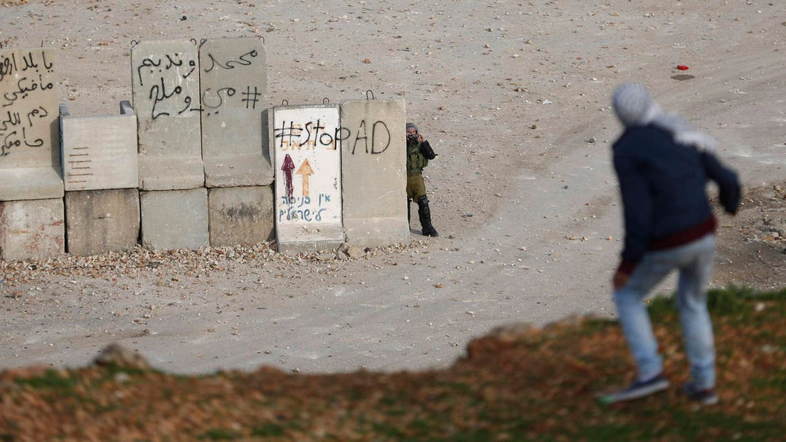 An Israeli soldier uses a camera to film Palestinian stone-throwers during clashes near Israel's Ofer Prison, near the West Bank city of Ramallah January 2, 2015.  (Reuters)