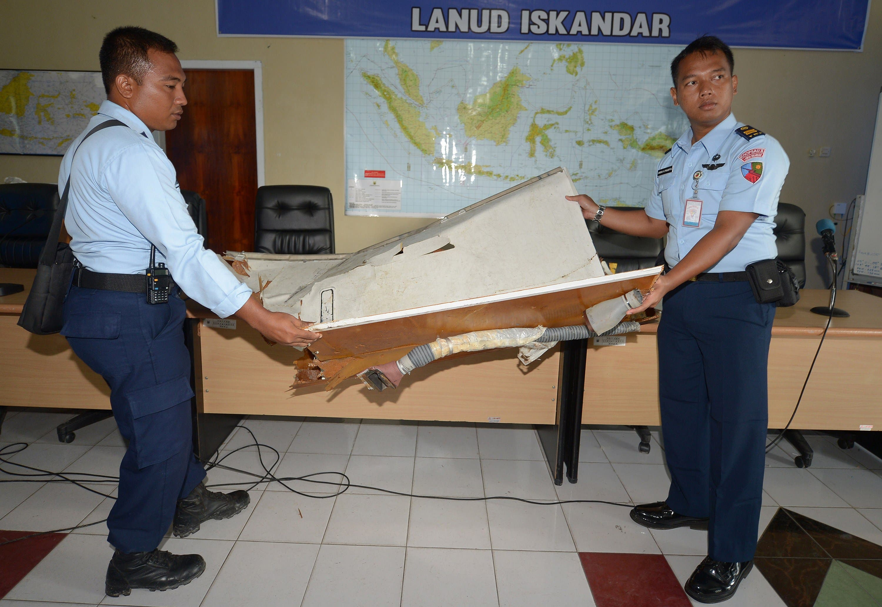 Indonesian military officers examine a piece of wreckage from AirAsia flight QZ8501, at the military base in Pangkalan Bun, the town with the nearest airstrip to the crash site, on January 2, 2015. (AFP)  Airasia wreckage