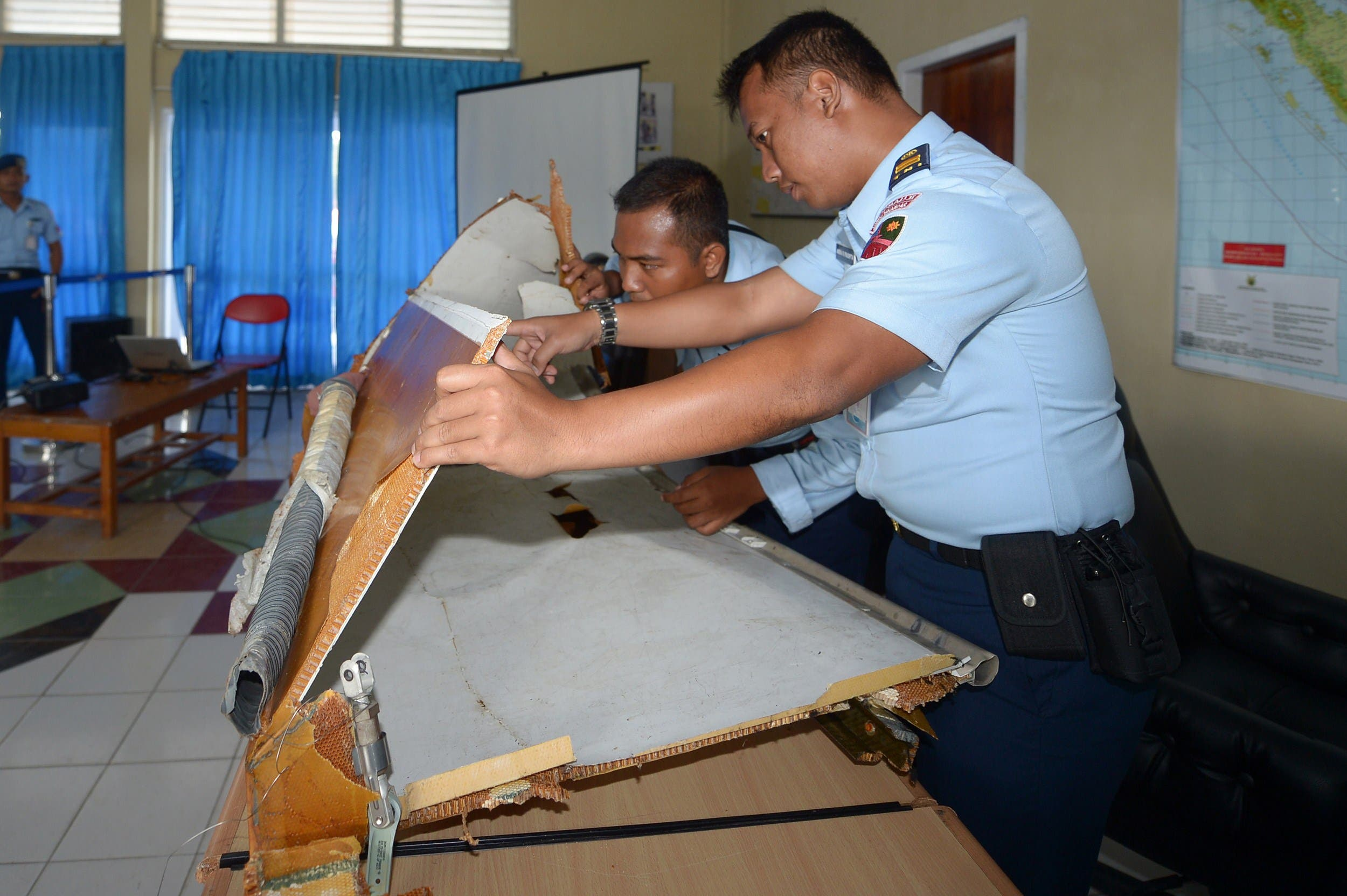 Indonesian military officers examine a piece of wreckage from AirAsia flight QZ8501, lost over the Java Sea, at the military base in Pangkalan Bun, the town with the nearest airstrip to the crash site, in Central Kalimantan on January 2, 2015. (AFP)