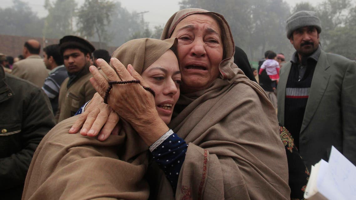 Mother (L) and grandmother of Muhammad Ali Khan, a student who was killed during an attack by Taliban gunmen on Army Public School, mourn during the visit of Imran Khan, chairman of Pakistan Tehrik-e-Insaf (PTI) political party, at the school in Peshawar December 22, 2014.