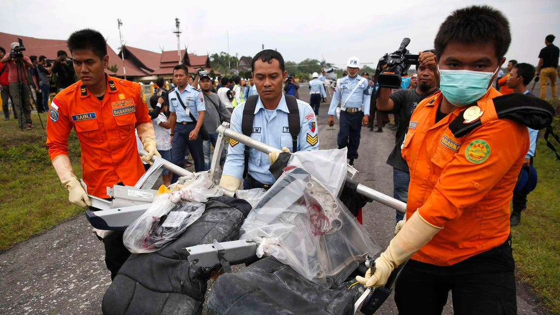 Parts of AirAsia QZ8501, recovered from the Java Sea, are carried by Indonesian Airforce and Search and Rescue crew members after they were offloaded from a U.S. Navy helicopter at the airport in Pangkalan Bun, Central Kalimantan January 5, 2015. (Reuters)