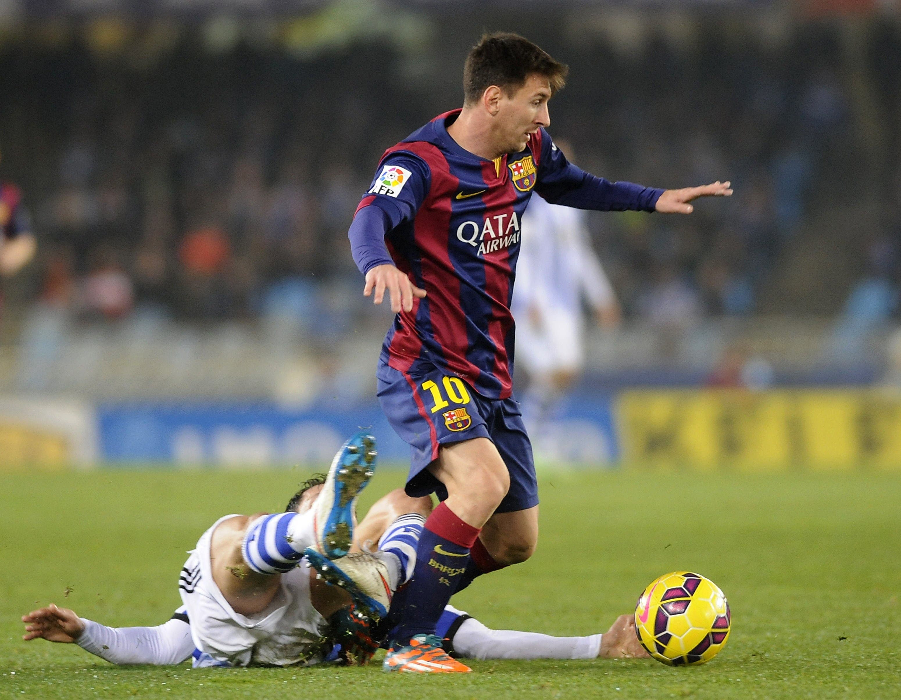 Barcelona's Argentinian forward Lionel Messi (R) vies with Real Sociedad's defender Alberto de la Bella (L) during the Spanish league football match Real Sociedad de Futbol vs FC Barcelona at the Anoeta stadium in San Sebastian on Jan.  4, 2015. (AFP)