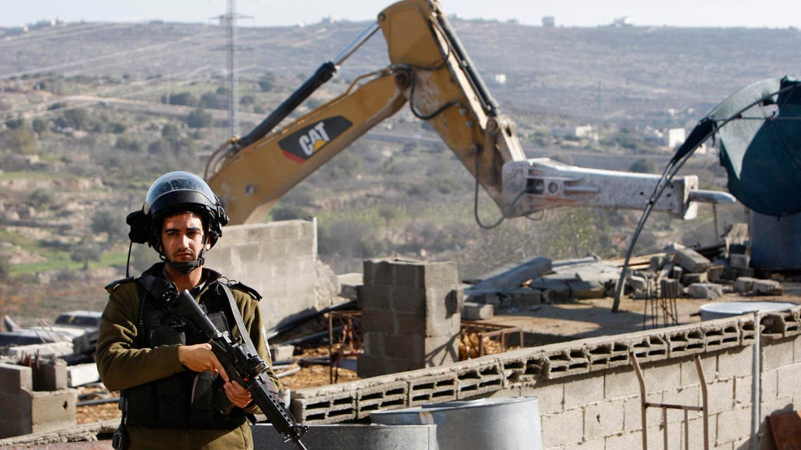 An Israeli policeman stands guard during the demolishing of a stockade owned by Palestinians in the West Bank city of Hebron January 5, 2015.  (Reuters)