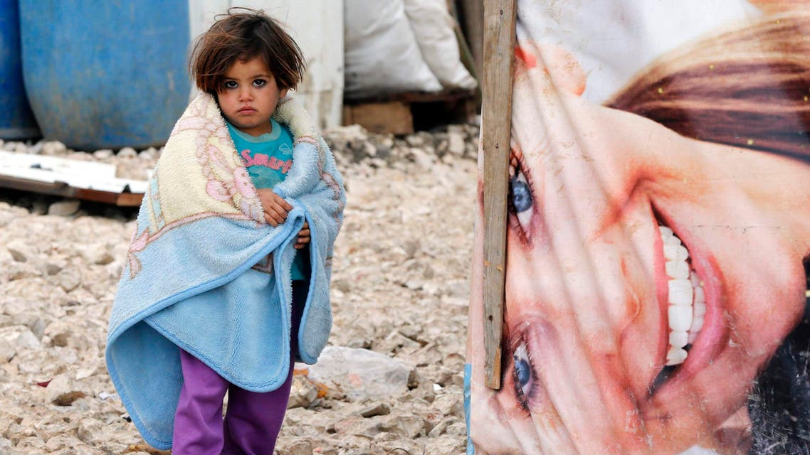 A Syrian refugee girl covers herself with a blanket as she stands outside tents at a makeshift settlement in Bar Elias in the Bekaa valley January 5, 2015. (Reuters)