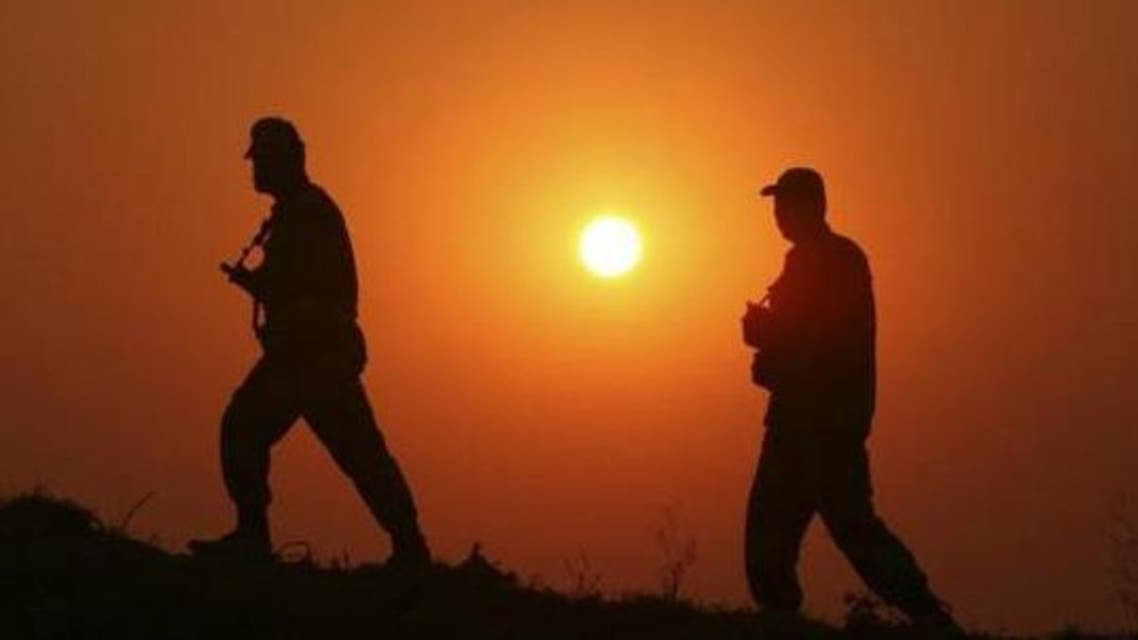 Border Security Force (BSF) soldiers patrol as they are silhouetted against the setting sun at the fenced border with Pakistan. (File photo Reuters)
