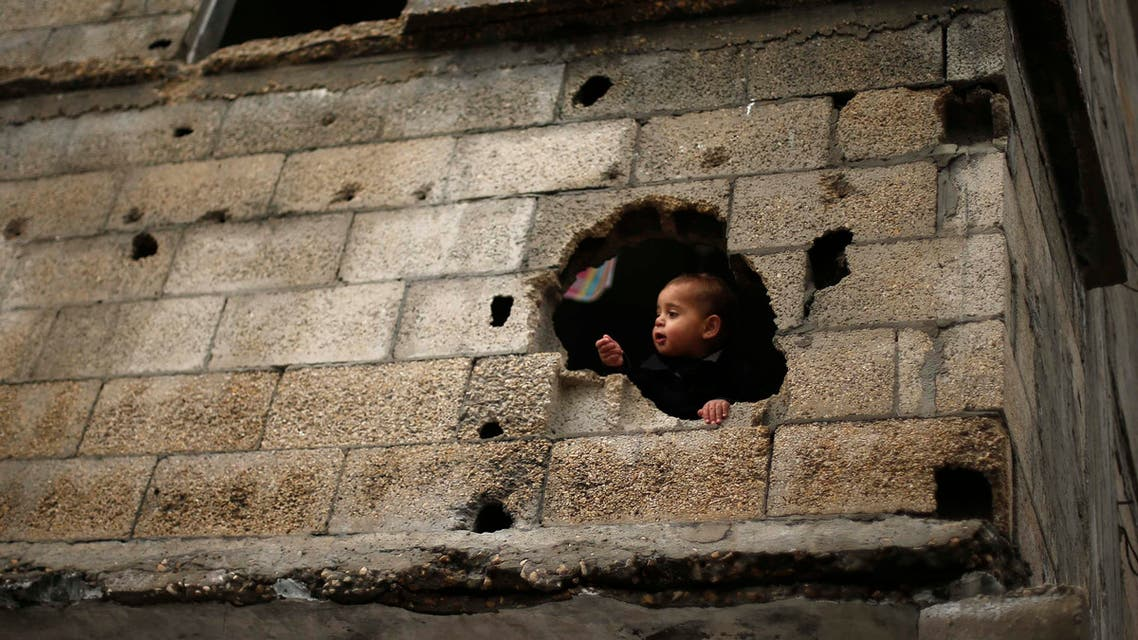 A Palestinian boy looks out through a hole in his family house witnesses said was damaged by Israeli shelling during the July-August Gaza war, Gaza City January 4, 2015. (Reuters)