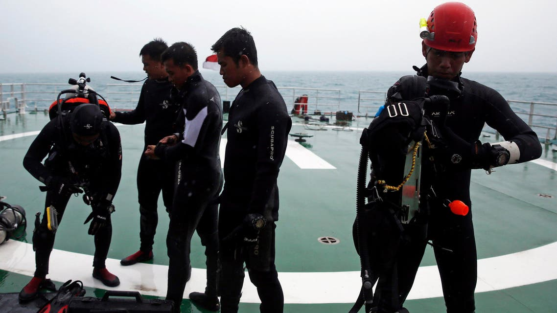 A group of divers prepares their gear on the deck of the Search and Rescue (SAR) ship KN Purworejo during a search operation for passengers onboard AirAsia Flight QZ8501 in the Java Sea January 4, 2015. (Reuters)