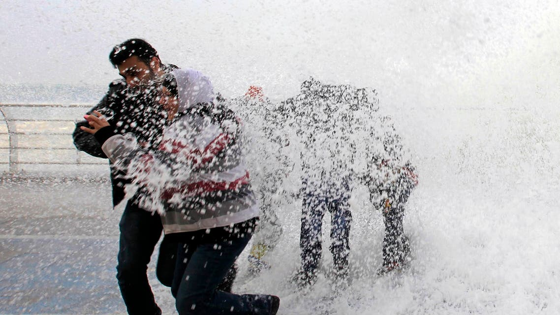 People play in front of a wave crashing into Beirut's Corniche, a seaside promenade, as high winds sweep through Lebanon ahead of an impending storm January 6, 2015. REUTERS