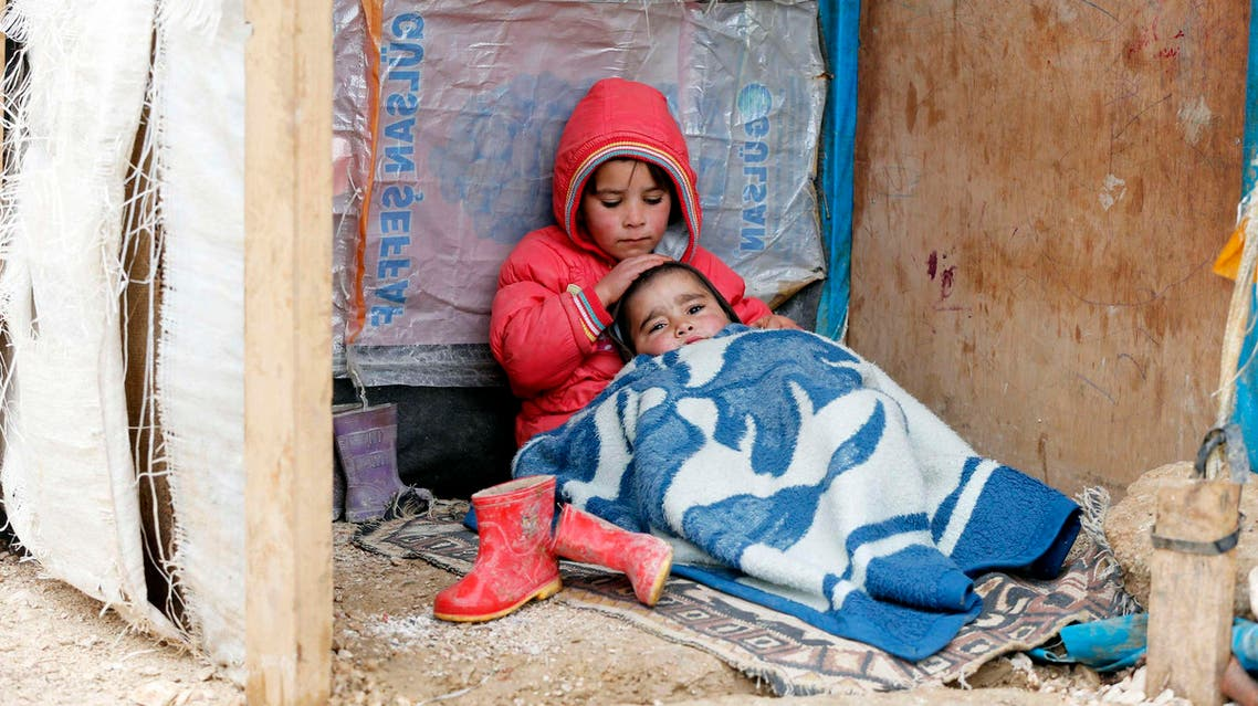 A Syrian refugee girl sits with her brother at a makeshift settlement in Bar Elias in the Bekaa valley. Reuters