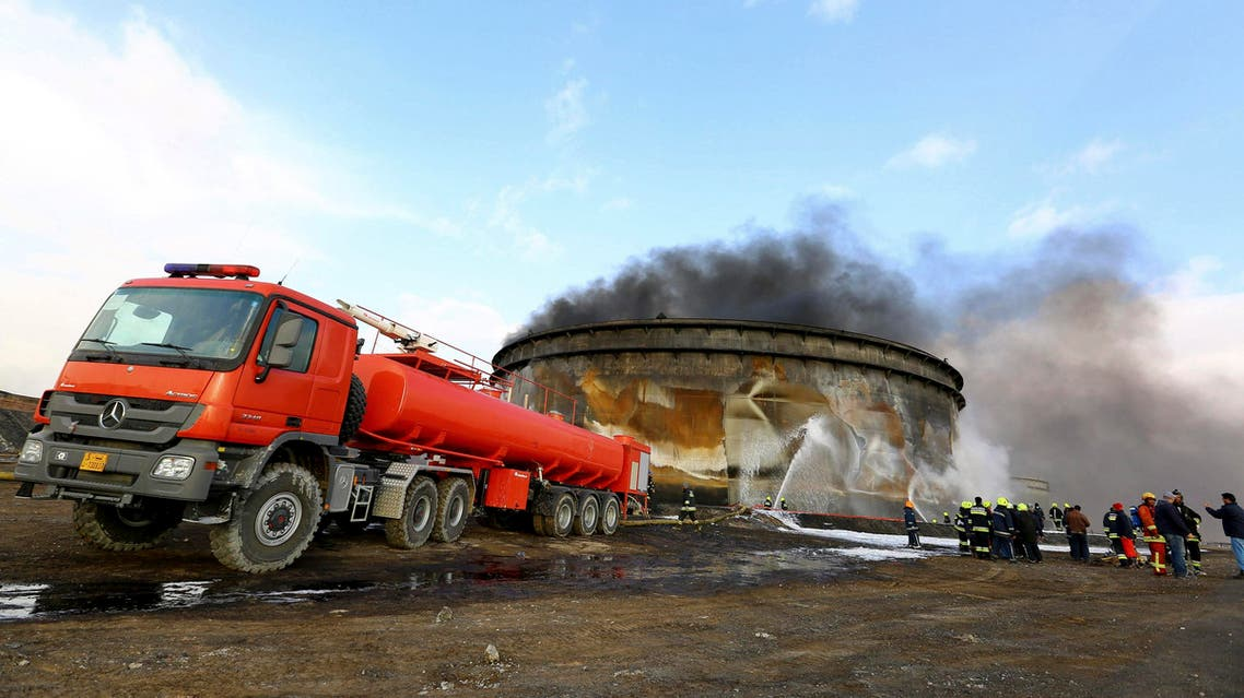 Fire-fighters work to put out a fire at a storage oil tank in the port of Es Sider January 2, 2015.  Reuters