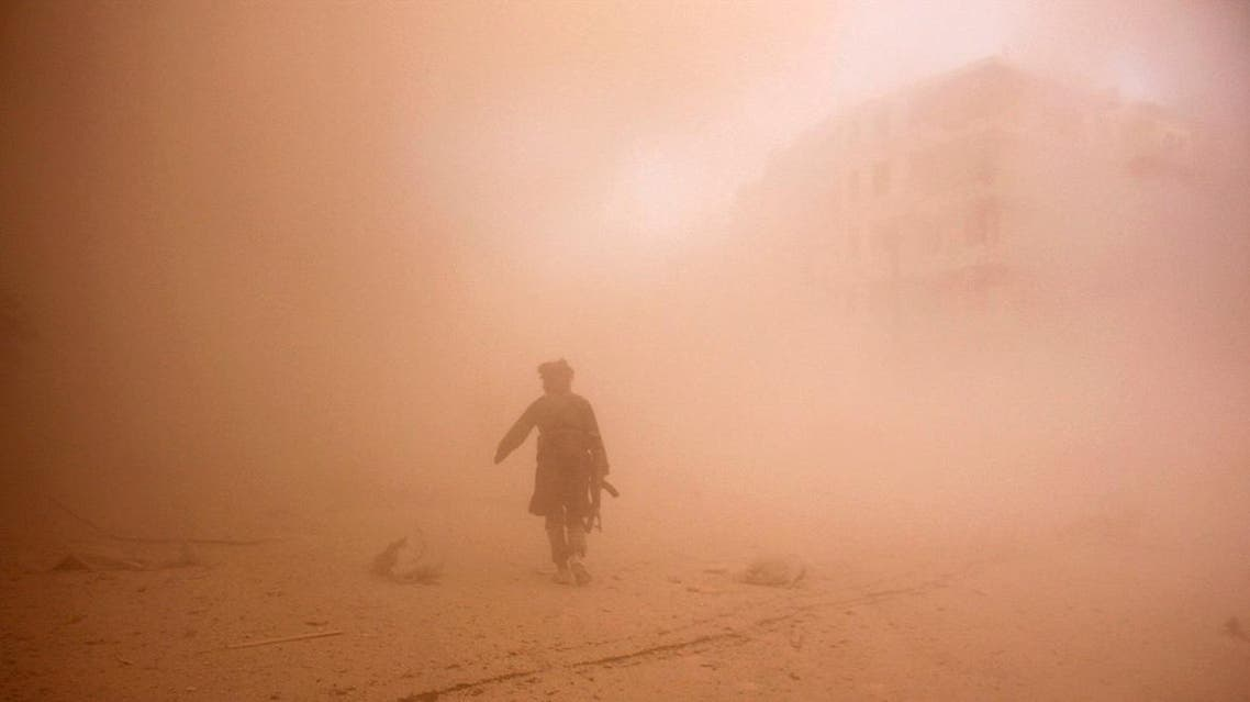 A rebel fighter runs through dust towards an area damaged by what activists said were barrel bombs dropped by warplanes loyal to Syria's President Bashar al-Assad in Aleppo. (Reuters)