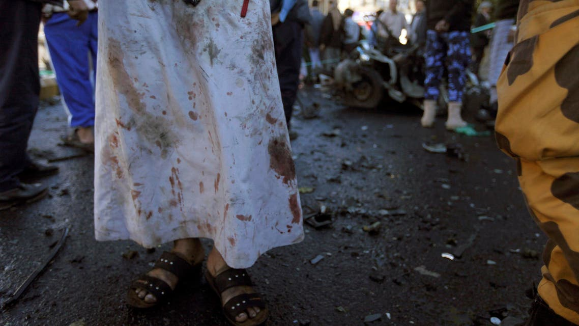 A medic with blood on his clothes stands at the scene of a car bomb attack outside the police college in Sanaa January 7, 2015.  (Reuters)
