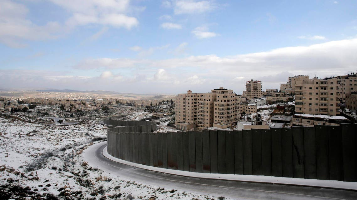 Snowfall is seen around a section of the controversial Israeli barrier that runs along the Shuafat refugee camp in the West Bank near Jerusalem January 8, 2015. (Reuters)