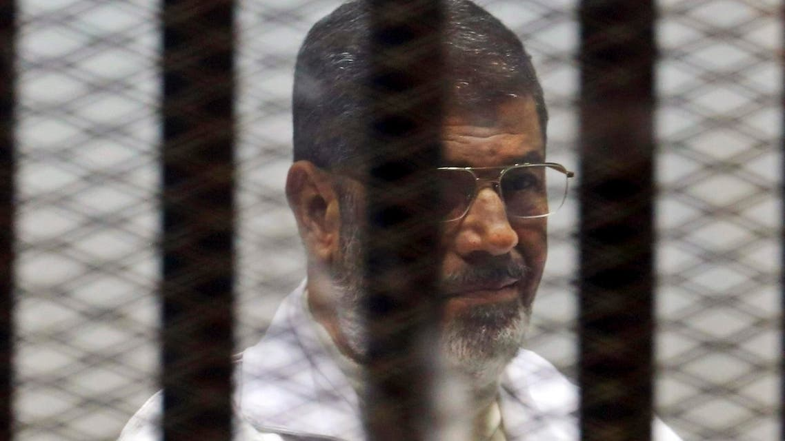 Former Egyptian President Mohamed Mursi sits behind bars with other Muslim Brotherhood members at a court in the outskirts of Cairo, December 29, 2014. (Reuters)