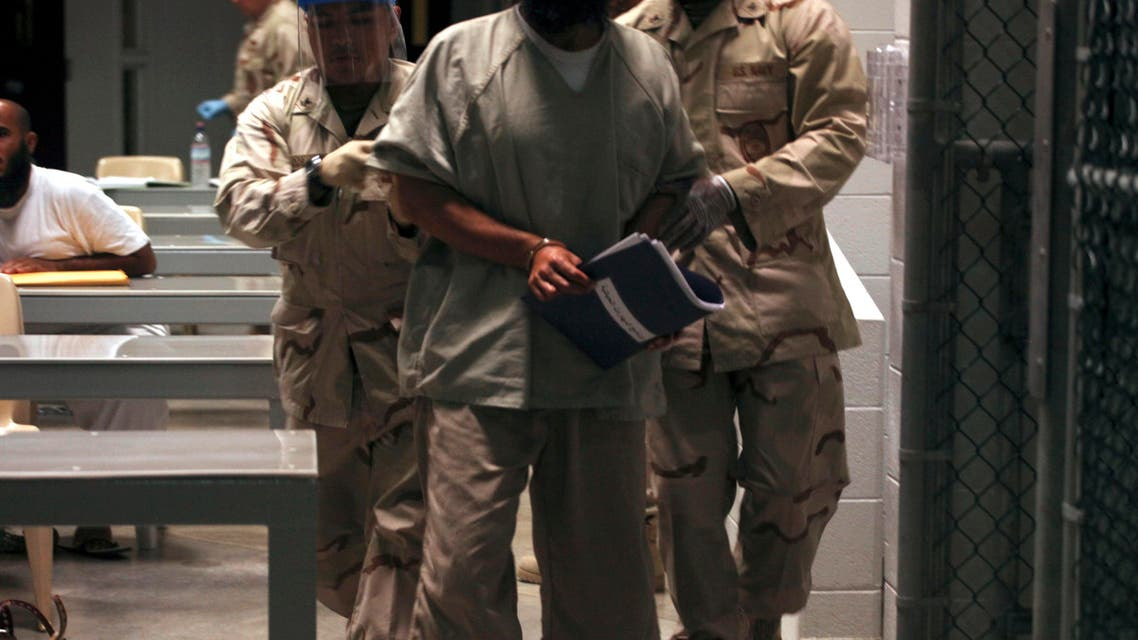 A Guantanamo detainee carries a workbook while escorted by guards who wear rubber gloves and face masks after attending a Life Skills class in the Camp 6 high-security detention facility on Guantanamo Bay U.S. Naval Base in Cuba. (File photo: AP)