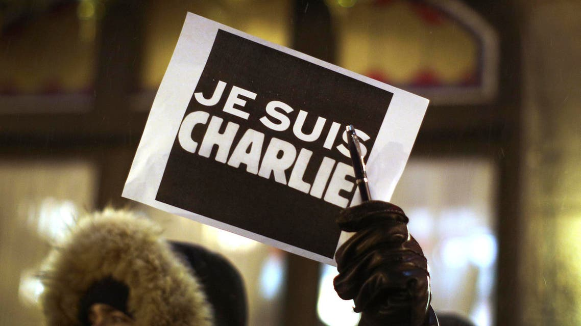 A man holds a pen with a sign during a vigil, for the victims of a shooting by gunmen at the offices of weekly satirical magazine Charlie Hebdo in Paris, at the French consulate in Quebec City, January 7, 2015. (Reuters)