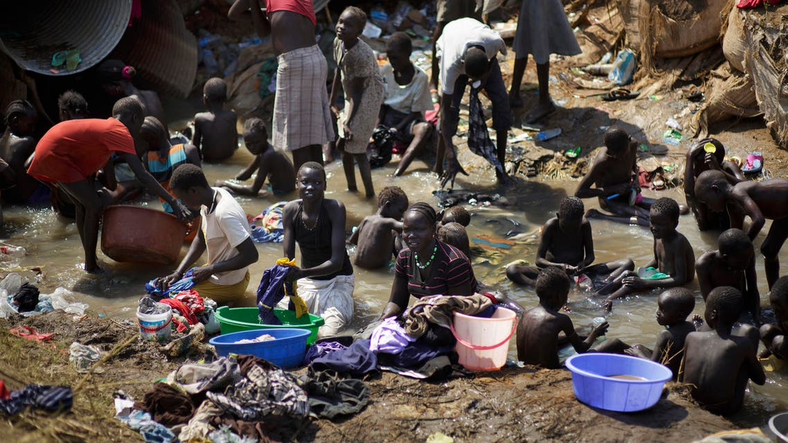 displaced people bathe and wash clothes in a stream inside a United Nations compound which has become home to thousands of people displaced by the recent fighting, in Juba, South Sudan. (File photo: AP)