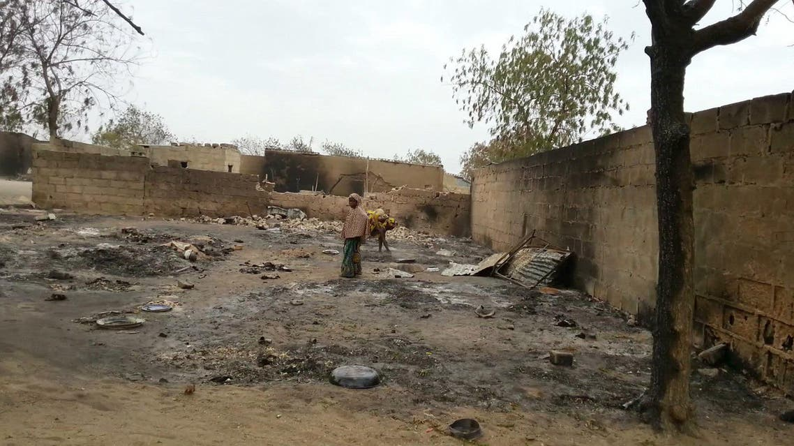 In this image shot with a mobile phone, a young girl stands amid the burned ruins of Baga, Nigeria, on Sunday, April 21, 2013. AP