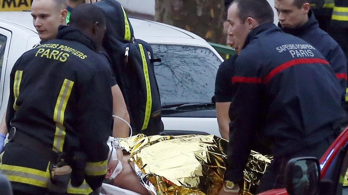 Rescue service workers and firefighters evacuate an injured person on a stretcher near the site of a shooting on the morning of January 8, 2015 in Montrouge, south of Paris.