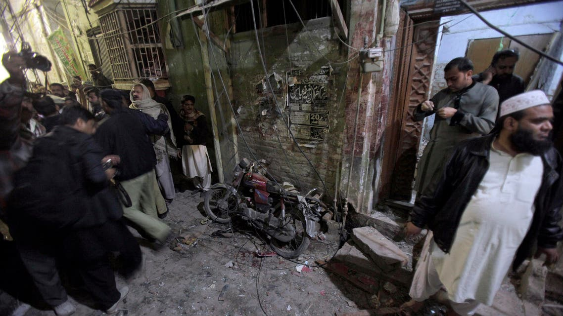 A Pakistani police officer and local residents gather next to a damage motorcycle at the site of a suicide bombing in Rawalpindi, Pakistan, Friday, Jan. 9, 2015. AP