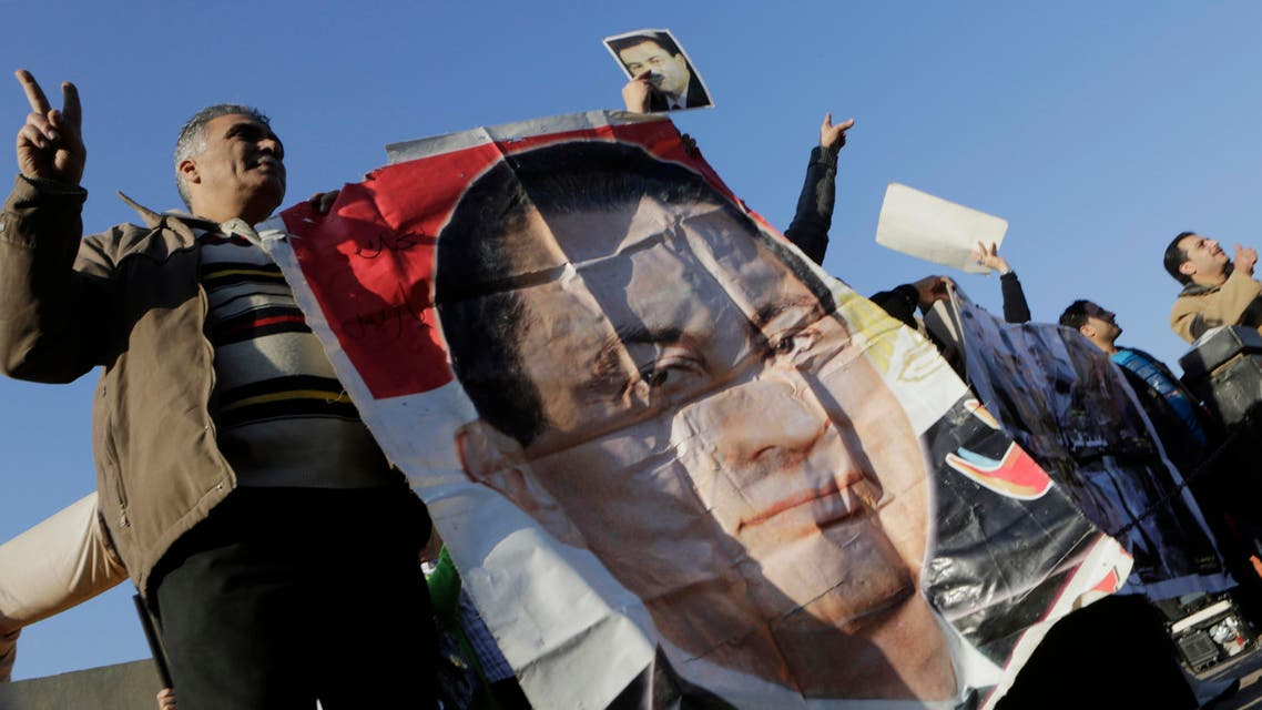 upporters of former Egyptian President Hosni Mubarak wave by his poster as he was taken by a helicopter ambulance from Maadi Military Hospital to a court in Cairo, Egypt, Saturday, Nov. 29, 2014. (File photo: AP)