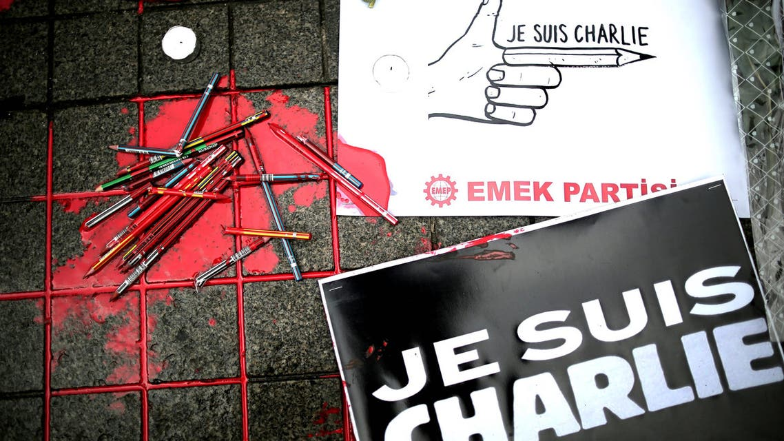 """Broken pens and placards that read: """"I am Charlie"""" lay on the ground as people gather outside the French consulate to pay tribute to the victims of the French satirical newspaper Charlie Hebdo, in Istanbul, Turkey, Friday, Jan. 9, 2015. (AP)"""