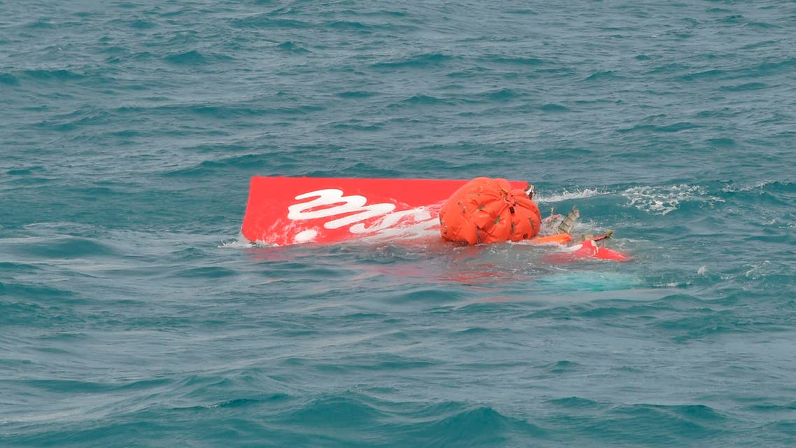 Part of the tail of AirAsia QZ8501 floats on the surface after being lifted as Indonesian navy divers conduct search operations for the black box flight recorders and passengers and crew of the aircraft, in the Java Sea January 10, 2015. (Reuters)