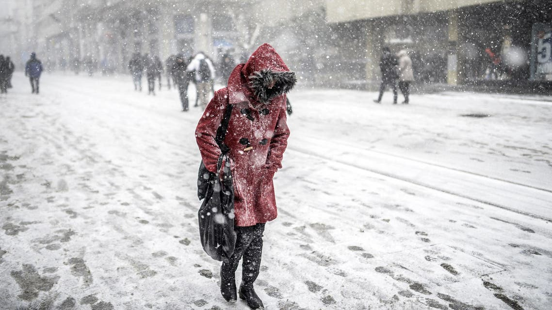 A woman walks under the snow in Istanbul on January 7, 2015. AFP