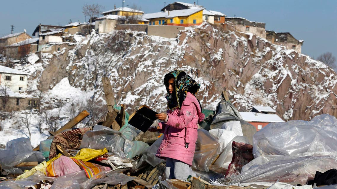 A Syrian refugee girl looks at a book she picked up from the debris of dismantled makeshift shelters of Syrian refugees, in the Hacibayram district of Ankara January 9, 2015. (Reuters)