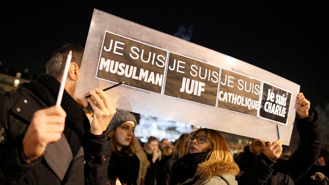 """People hold a placard which reads """"I am Muslim, I am Jewish, I am Catholic, I am Charlie"""" at a vigil in Paris January 8, 2015. (Reuters)"""
