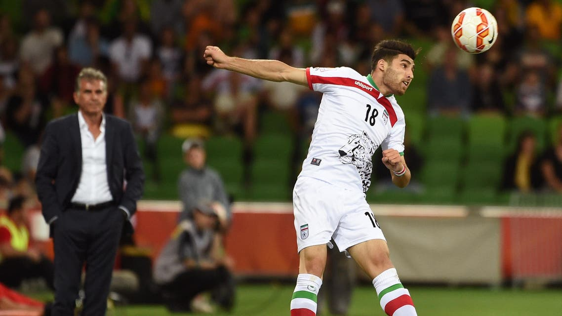 Iran's Alireza Jahan Bakhsh (R) heads the ball as coach Carlos Quieroz (L) looks on during their football match against Bahrain at the AFC Asian Cup in Melbourne on January 11, 2015.