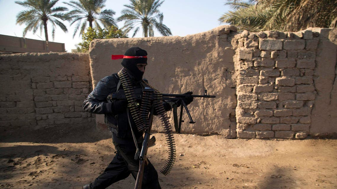 A fighter from the Shi'ite Kata'ib Imam Ali (Imam Ali Brigades) militia runs as they search a house after taking control of a village from