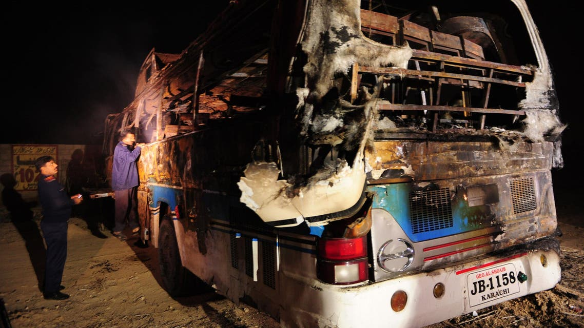 Pakistani volunteers search for victims inside a burnt out passenger bus after it collided with an oil tanker along the Super Highway near Karachi early on January 11, 2015. (AFP)