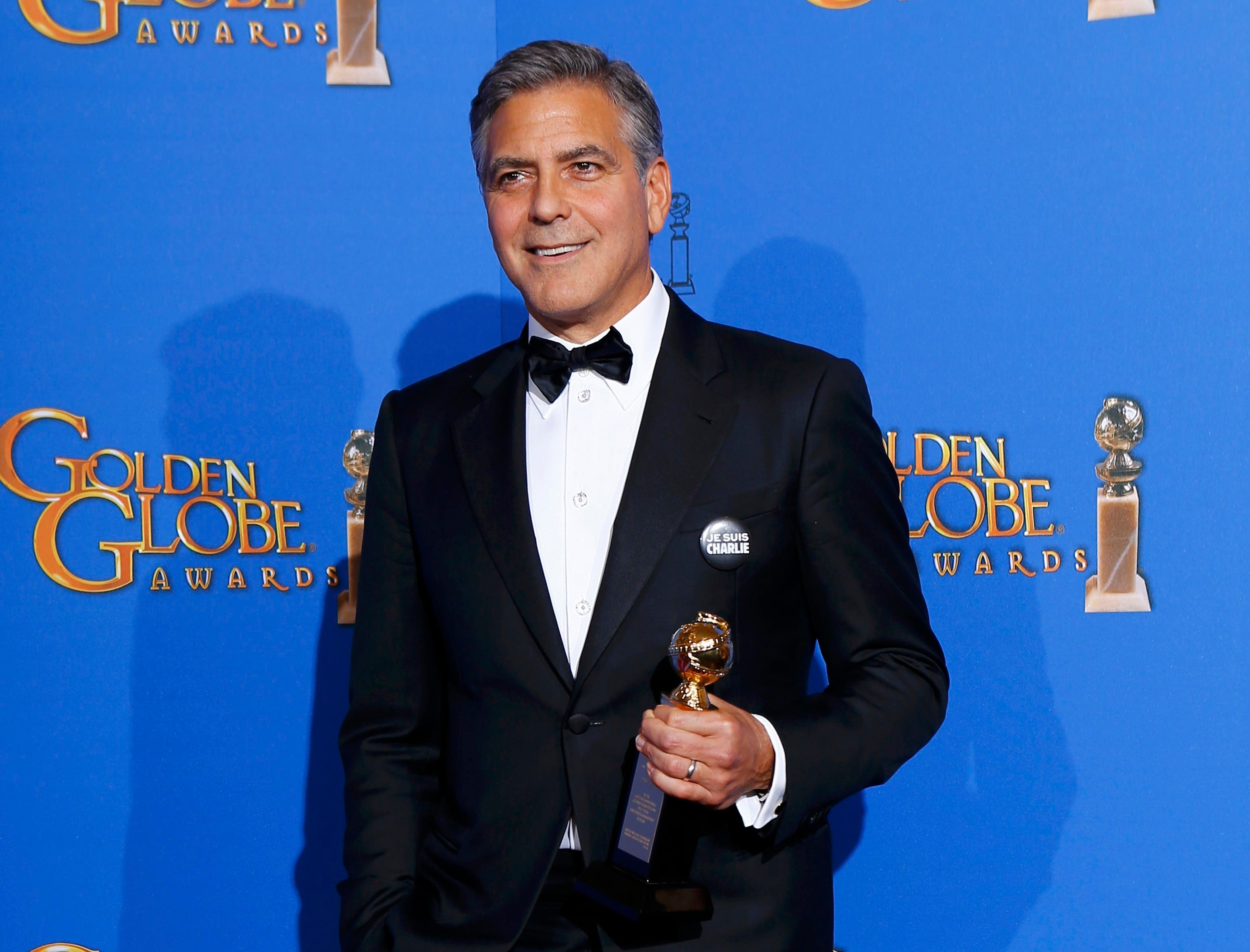 Honoree actor George Clooney poses with the Cecille B. DeMille award backstage at the 72nd Golden Globe Awards in Beverly Hills, California January 11, 2015. (Reuters)