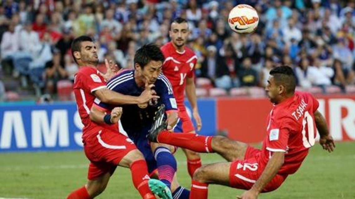 Japan's Yohei Toyoda is tackled by Palestine's Musab Battat, left, and Tamer Salah, right, during the AFC Asia Cup soccer match between Japan and Palestine in Newcastle, Australia, Monday, January 12, 2014. (AP Photo/Rob Griffith)