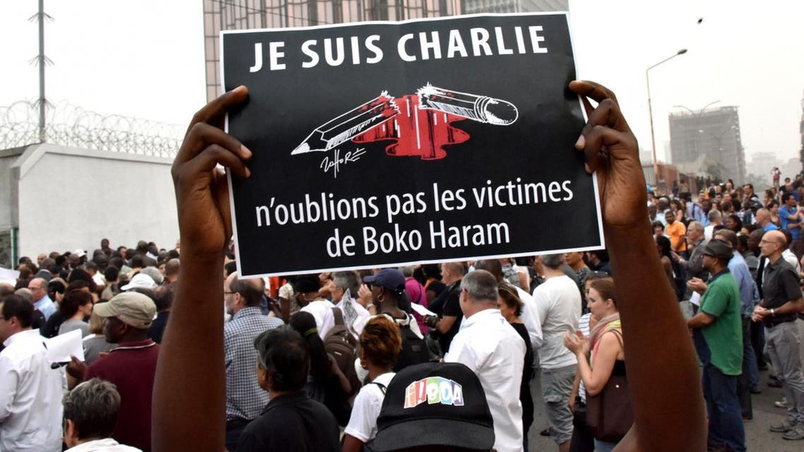 A man holds a placard that reads 'I am Charlie, let's not forget the victims of Boko Haram' outside the French embassy in Abidjan.  AFP