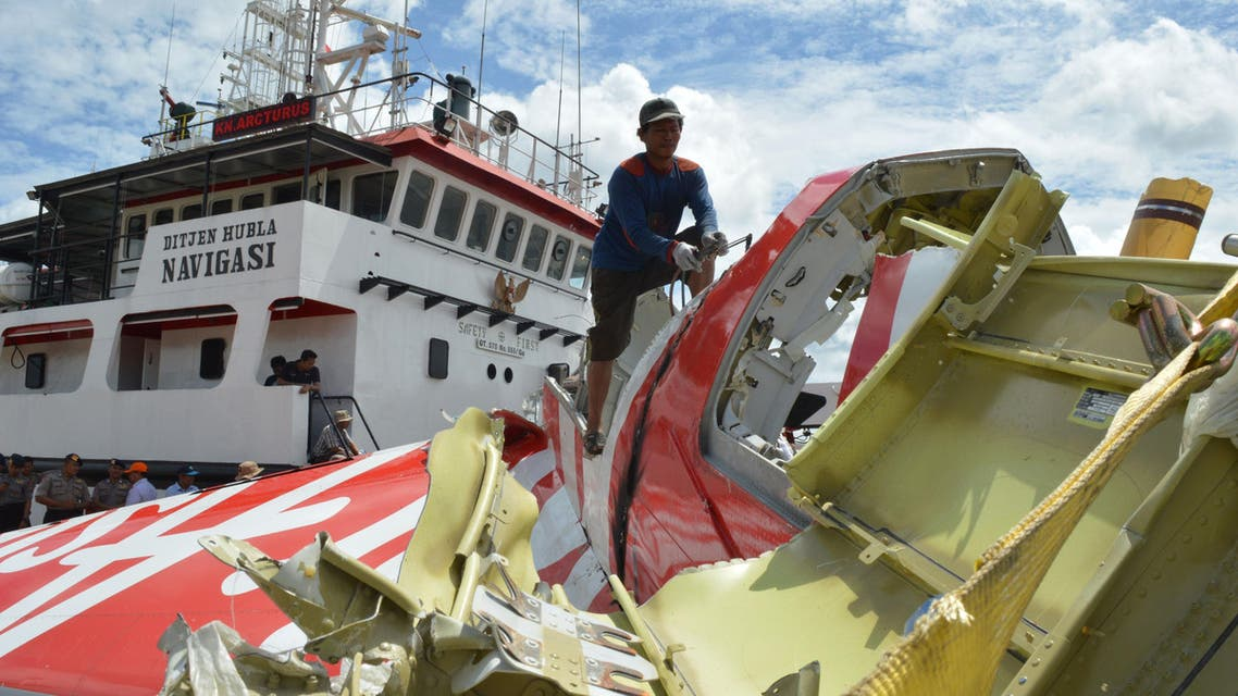 An Indonesian worker (top C) cuts the tail of the AirAsia flight QZ8501 in Kumai on January 12, 2015, after debris from the crash was retrieved from the Java sea. AFP