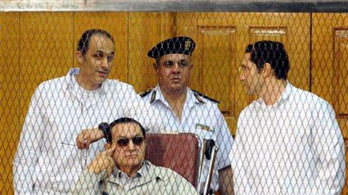In this Saturday, Sept. 14, 2013 file photo, former Egyptian President Hosni Mubarak, seated, and his two sons Gamal Mubarak, left, and Alaa Mubarak, right, attend a hearing in a courtroom at the Police Academy, Cairo, Egypt.