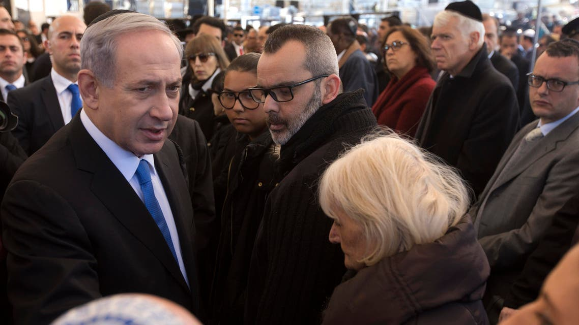 Israeli Prime Minister Benjamin Netanyahu, left, speaks briefly with relatives of Yoav Hattab, one of four French Jews killed in an attack on a kosher grocery store in Paris last week, during their funeral service, in Jerusalem, Tuesday, Jan. 13, 2015. AP