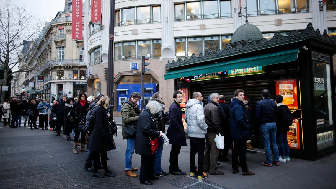 """People queue to get a copy of satirical French magazine Charlie Hebdo new issue titled """"Tout est pardonne"""" (""""All is forgiven"""") showing a caricature of Prophet Mohammad in front of a kiosk in Paris Jan. 14, 2015. (Reuters)"""