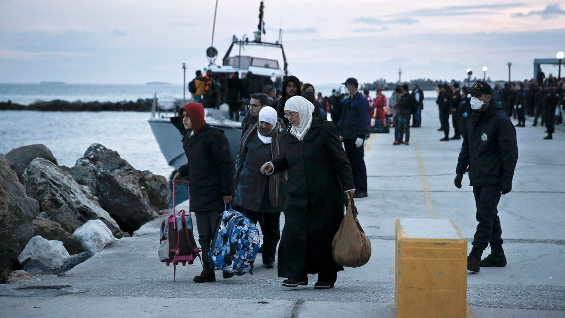 In this Nov. 27, 2014 file photo, women walk with their belongings just after disembarking from a crippled freighter carrying hundreds of refugees trying to migrate to Europe. File Photo AP
