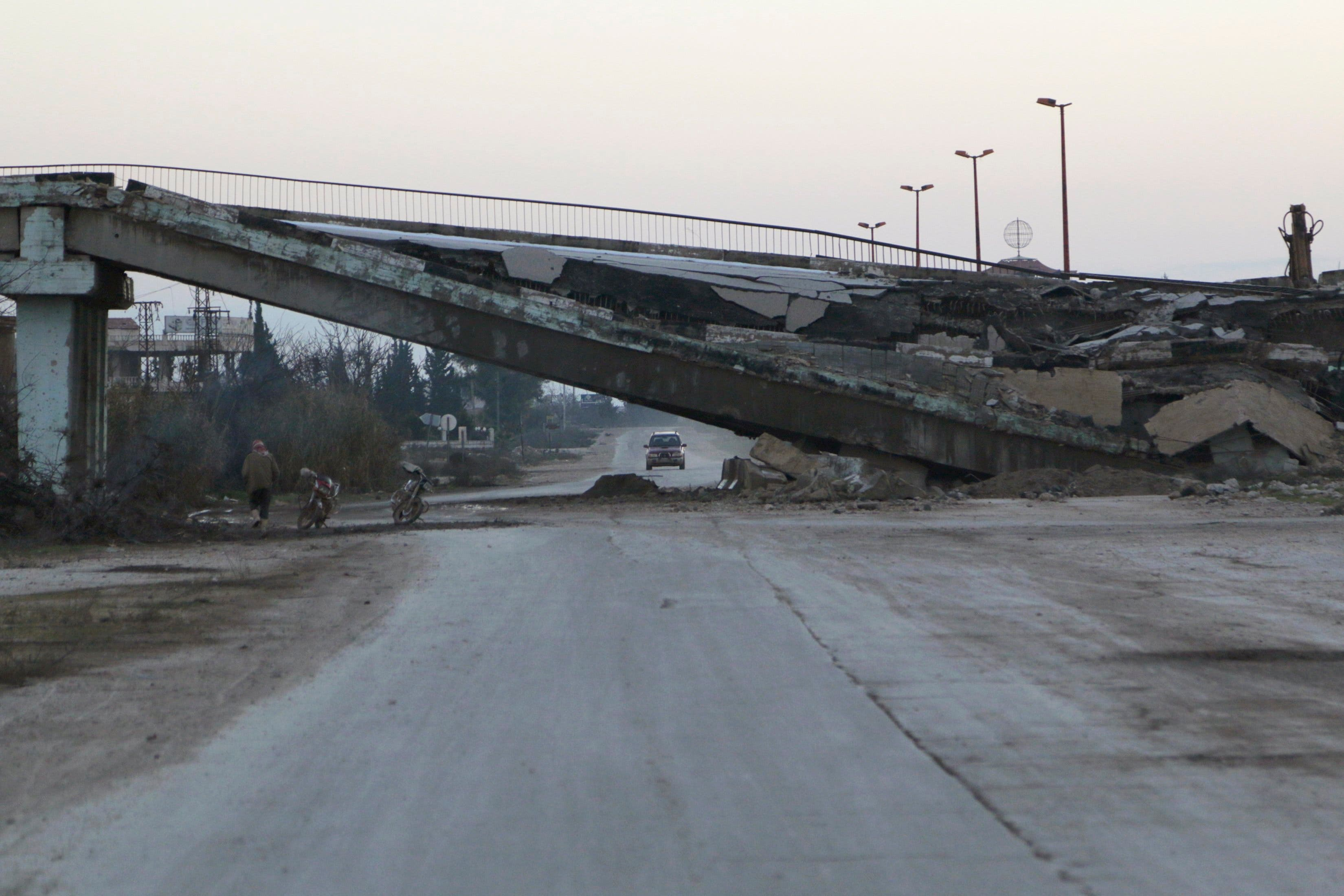 Residents drive by a damaged bridge on a highway that connects Aleppo with Damascus in Maaret al-Naaman town in Idlib province Jan. 14, 2015.  (Reuters)