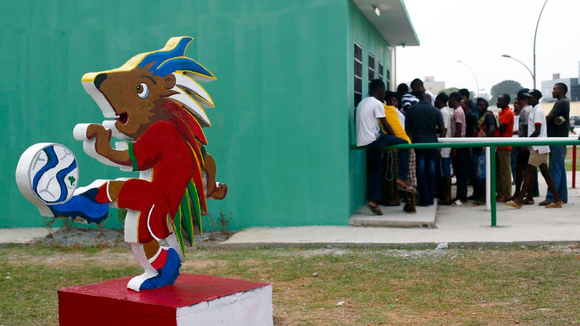 """Chuku Chuku, the official mascot of the tournament is seen as fans wait in line to buy tickets for the upcoming African Nations Cup outside the Estadio de Bata """"Bata Stadium"""" which will host the opening ceremony on Saturday, in Bata Jan. 15, 2015.  (Reuters)"""