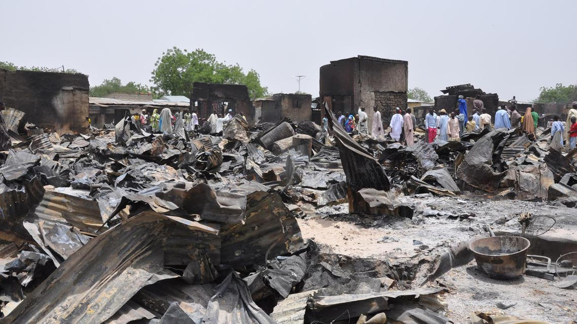 people stand outside burnt houses following an attack by Islamic militants in Gambaru, Nigeria. File AP