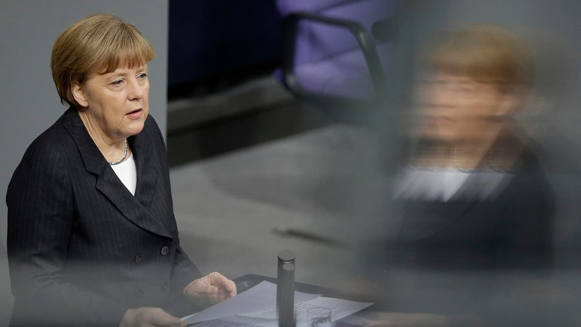 German Chancellor Angela Merkel is reflected in a window of the visitors' tribune as she speaks during a meeting of the German federal parliament, Bundestag, in Berlin, Germany, Thursday, Jan. 15, 2015.  (AP)